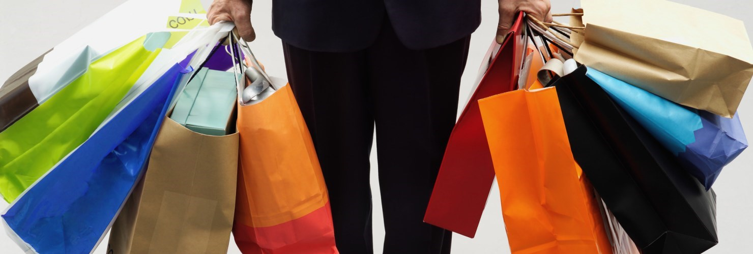 Image of lower half of person holding many shopping bags
