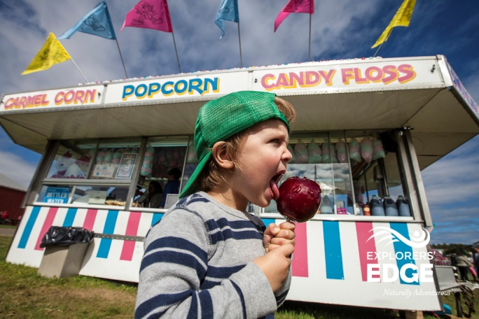 Boy eating candy apple at fall fair