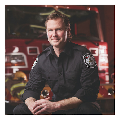 Image of Patrick Mathieu sitting in front of a firetruck