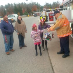 A firefighter handing out goody bags to two small girls.